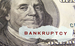 Bankruptcy. Text on a paper scrap over one hundred dollar bill Royalty Free Stock Image