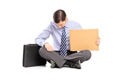 Bankrupted businessperson begging with a piece of cardboard Stock Photos
