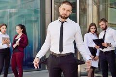 bankruttt En ung man i svart byxa och demoner för en vitskjorta royaltyfri foto