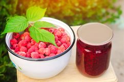 Banks with fragrant homemade raspberry jam in the garden. summer harvest. sweet food. food stock for the winter. countryside, outd. Oor. nature royalty free stock photography