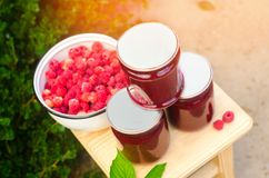 Banks with fragrant homemade raspberry jam in the garden. summer harvest. sweet food. food stock for the winter. countryside, outd. Oor. nature royalty free stock photos