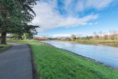 Banks of the Manawatu River in Palmerston North New Zealand. With grass on the banks under a brilliant blue sky with clouds royalty free stock photos
