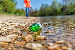 On the banks of the river is a glass bottle thrown by someone. In the background is a volunteer. The concept of environmental stock photography