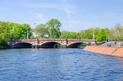 Banks of the river Spree and the Luther Bridge in Berlin. Berlin, Germany - April 22, 2018: Banks of the river Spree with citizens enjoying the warm spring day Stock Photo
