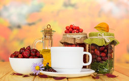 Banks with rowan berries, rose hips,  oil and cup  tea. Royalty Free Stock Images