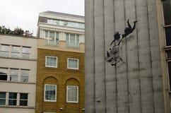 Banksy fallande shoppare och spårvagn Arkivbild