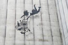 Banksy falling shopper graffiti royalty free stock photo