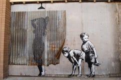 Banksy que olha grafittis dos meninos Imagens de Stock