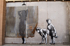 Banksy som kikar pojkegrafitti Arkivbilder