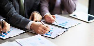 Bankzaken of financieel analist de grafieken van de Desktopboekhouding, pennen wijst op in de grafiek royalty-vrije stock foto's