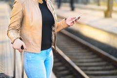 Banlieusard à l'aide du smartphone dans la station de train photo libre de droits