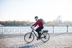 Banlieusard d'homme d'affaires de hippie avec la bicyclette électrique voyageant au travail dans la ville images libres de droits