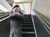 Banlieusard sur un escalator Photos stock