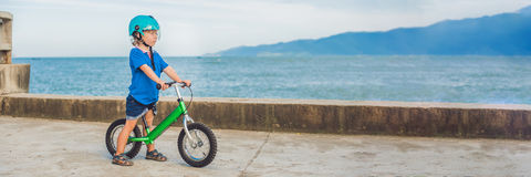 BANNER Active blond kid boy driving bicycle in the park near the sea. Toddler child dreaming and having fun on warm summer day. ou. Tdoors games for children stock images
