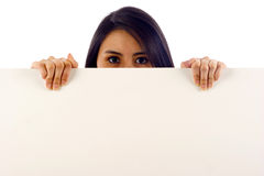 Banner Ad. Beautiful hispanic woman behind a banner ad -Isolated over a white background Royalty Free Stock Photography