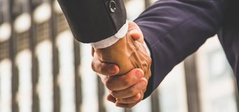 Free Banner And Header Panoramic Horizontal - Close Up Businessmen Shaking Hands And Handing Down Business Deals In Urban Center, Stock Photo - 161041640