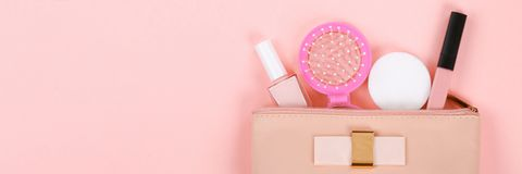 Beauty set with decorative cosmetics. nail polish, brushes and bag on pink background top view mockup stock photo