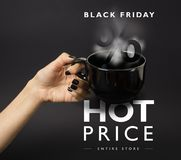 Banner for Black Friday sale - female hand with black nails holding a big, black, steaming cup. Royalty Free Stock Image