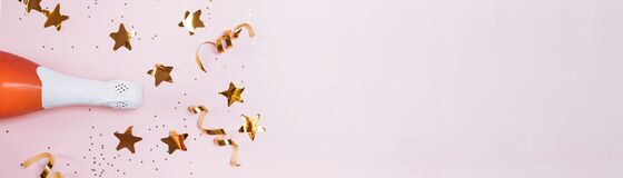 Banner with with bottle of rose champagne and golden star confetti