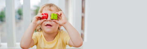 BANNER The boy makes eyes of colorful children`s blocks. Cute little kid boy with glasses playing with lots of colorful plastic b stock photography