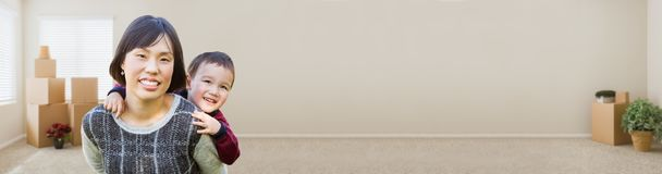 Banner of Chinese Mother and Mixed Race Child Inside Empty Room. With Moving Boxes and Plants Royalty Free Stock Photography