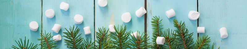 Banner of Christmas border with branch of fir tree and marshmallows on wooden background. Top view copy space stock photos