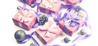 Banner Christmas boxes with gifts on the occasion of pink color on white background cones nuts decor Top view flat lay horizontal. Banner Christmas boxes with stock photos