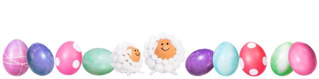 Banner, colorful dyed easter eggs and two funny lamb shaped eggs royalty free stock photo