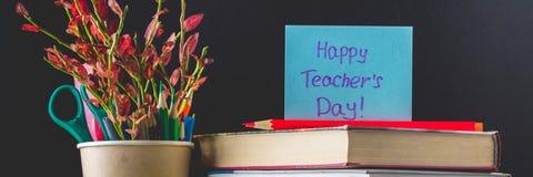 banner Concept Leraars\ 's Dag Voorwerpen op een bordachtergrond Boeken, groene appel, plaque: Gelukkige Leraars\ 's Dag, potlode stock foto