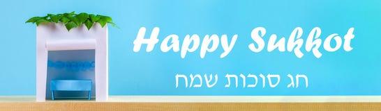 banner De tekst in Hebreeër is Gelukkige Sukkot Een hut van document wordt met bladeren op een blauwe achtergrond wordt behandeld royalty-vrije stock foto