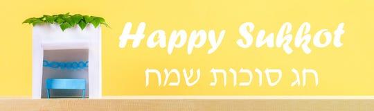 banner De tekst in Hebreeër is Gelukkige Sukkot Een hut van document wordt met bladeren op een gele achtergrond wordt behandeld g stock foto's