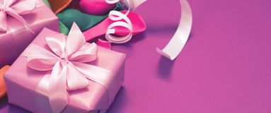 Banner Decorative box composition with gifts satin ribbon bow inflatable balls serpentine purple background A top view. Banner Decorative box composition with stock images