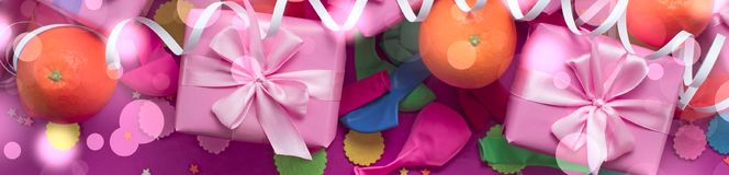 Banner Decorative composition Three boxes with gifts Satin ribbon Bow Oranges Confetti Serpentine birthday party. The view from the top stock photos