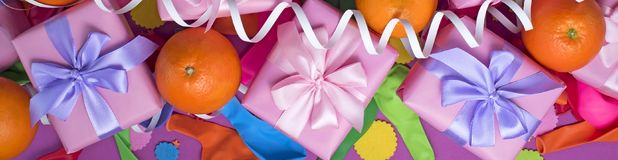 Banner Decorative composition Three boxes with gifts Satin ribbon Bow Oranges Confetti Serpentine birthday party. The view from the top royalty free stock photography