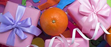 Banner Decorative composition Three boxes with gifts Satin ribbon Bow Oranges Confetti Serpentine birthday party. The view from the top royalty free stock photos