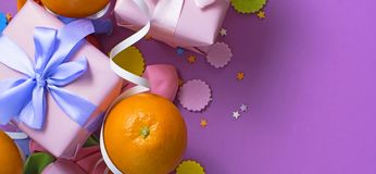 Banner Decorative composition Two boxes with gifts Satin ribbon Bow Oranges Confetti Serpentine birthday party. The view from the top stock photo
