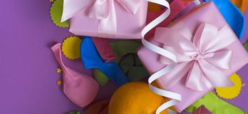 Banner Decorative composition Two boxes with gifts Satin ribbon Bow Oranges Confetti Serpentine birthday party. The view from the top royalty free stock image