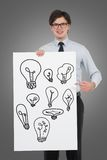 Banner with drawing bulbs. Businessman holding banner with drawing bulbs Stock Photography