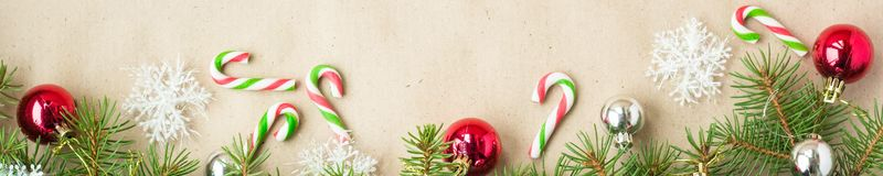 Banner of Festive christmas border with red and silver balls on fir branches and snowflakes on rustic beige background. With copyspace and pen stock photo