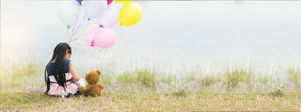 Banner Happy Child hug teddy bear hold air balloon green park playground. Teddy bear best friend little girl. Autism happy play