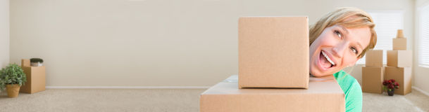 Banner of Happy Young Adult Woman Holding Moving Boxes In Empty Stock Images