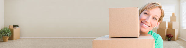 Banner of Happy Young Adult Woman Holding Moving Boxes In Empty Royalty Free Stock Photography