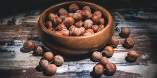 Banner. Hazelnuts nuts in a wooden bowl on a dark background. Low key lighting royalty free stock images