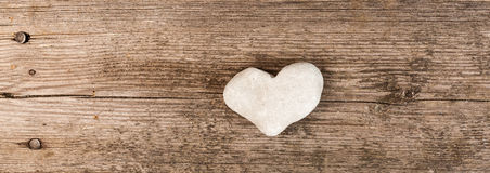 Banner with a heart of stone on wooden background. Horizontal web banner with a white stone shaped as a heart on wooden background Stock Image