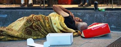 Homeless man sleeps on the street stock images