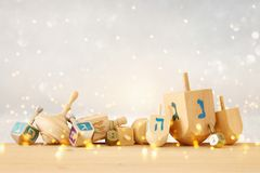 Banner of jewish holiday Hanukkah with wooden dreidels & x28;spinning top& x29; over glitter shiny background. stock photo