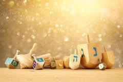 Banner of jewish holiday Hanukkah with wooden dreidels & x28;spinning top& x29; over glitter shiny background. Banner of jewish holiday Hanukkah with wooden