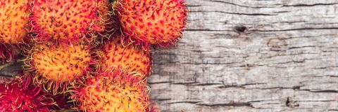 BANNER, Long Format Fresh rambutan fruit on wooden teble background, closeup, fruit in Thailand.  Royalty Free Stock Images