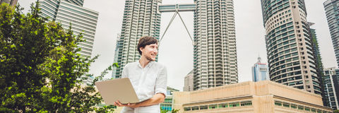 BANNER Man businessman or student in casual dress using laptop in a tropical park on the background of skyscrapers. Mobile Office. BANNER Man businessman or Stock Image