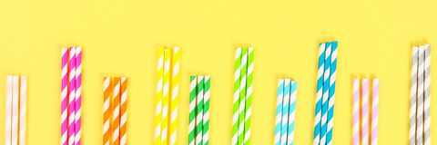 Multi-colored straw paper tubes on a bright yellow pastel background. Top view, copy space. Banner. Multi-colored straw paper tubes on a bright yellow pastel royalty free stock photo